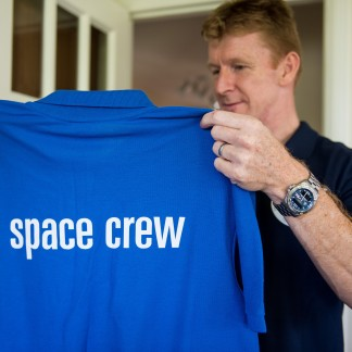 Tim holding a space crew t-shirt